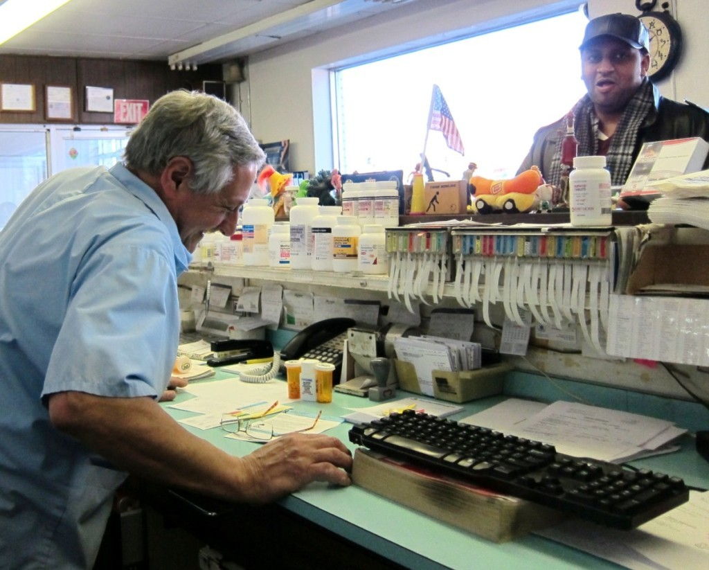 Pharmacist Richard Sabatelli, owner of Lawson's since 1983,  shares a laugh with a customer.