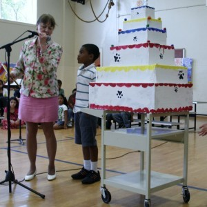 Hyattsville Elementary School recently marked its 95th birthday as well as the end of the school year. At a party on June 2, principal Jeanne Washburn, who is retiring, adjusts the microphone for rising second-grader Ellis Hollingsworth. Photo courtesy Valerie Russell.