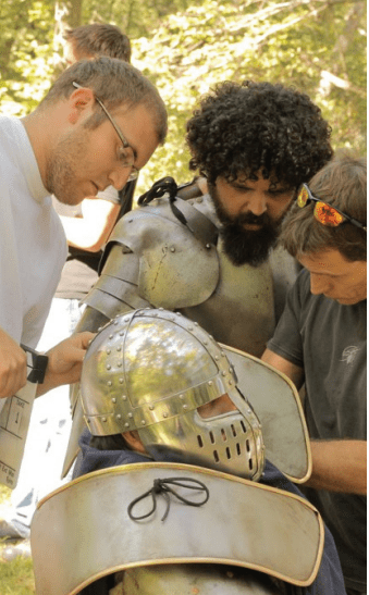 For his latest project, a web series that debuted on  March 10, filmmaker Francis Abby recruited fellow St. Jerome and DeMatha grad Matt Creger.  Creger, at left, helps adjust a helmet for one of the actors. Photo courtesy Francis Abbey.