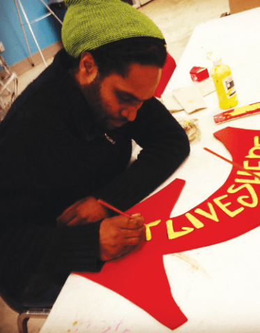 Nehemiah Dixon III, Visual Arts Coordinator at Joe's Movement Emporium, designing the Art Lives Here arrow. Photo courtesy Art Lives Here.