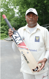 Waqas Shahid, who has competed at the national level, shows off his cricket bat. Shahid plays for the Virginia Cricket Club, shown here warming up on the field. Photo by Megan J. Brockett.