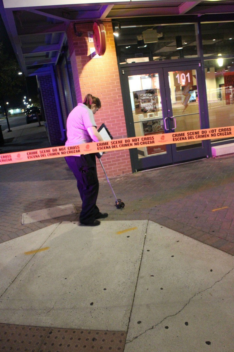 An evidence technician at work at the crime scene late Saturday evening.